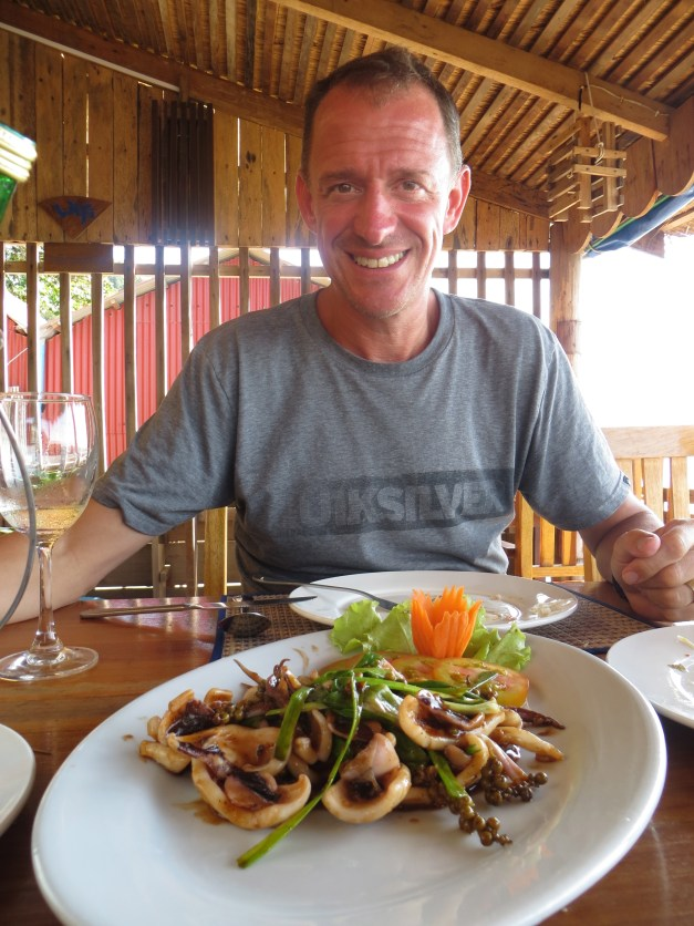 Mark enjoying calamari with Kampot pepper at the crab market in Kep