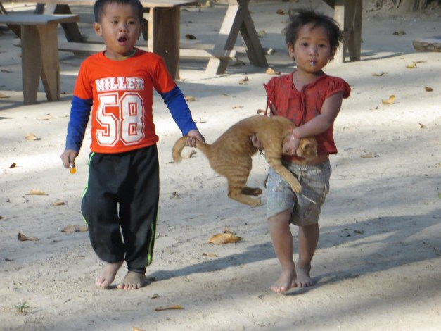 After you go through the cave and continue up river a bit, you stop and take a break at a small Laotian village. Mark caught these kids taking their cat for a walk.