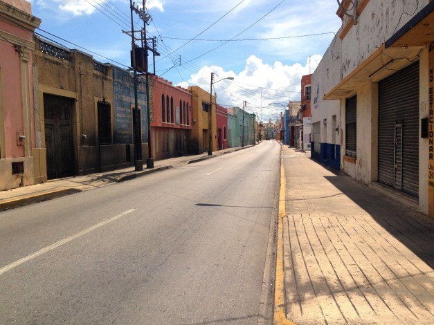 The nearly deserted streets of Mérida heading directly into the main square at mid-day. With the sun directly overhead there were no shadows, no place to hide, and not a lot of activity.