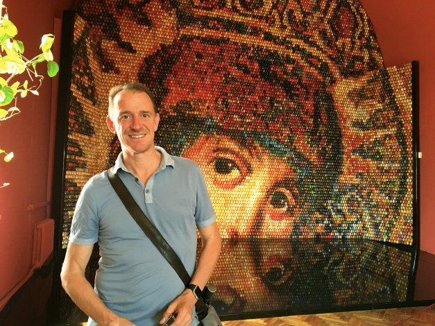 "Mark in front of a mosaic titled  ""Looking Into Eternity "" by Ukrainian artist Oksana Mas, displayed in a museum on the grounds of St. Sophia. It's made from 15,000 individually painted Easter eggs."