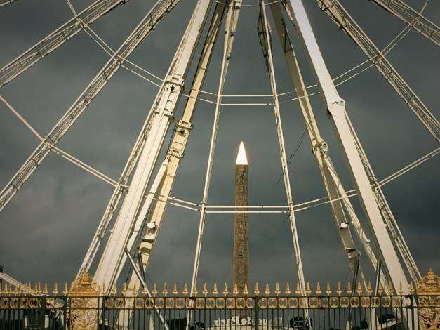 And a very artsy picture of the ancient Egyptian obelisk in the Place de la Concorde, seen through the spokes of a giant Ferris Wheel
