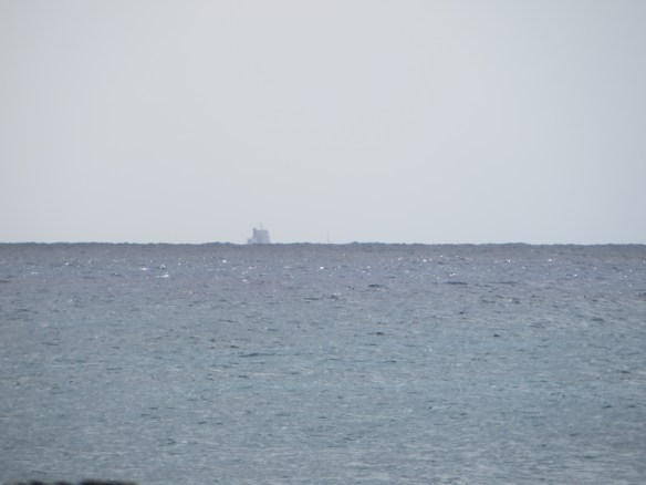 Only the superstructure is visible over the horizon.