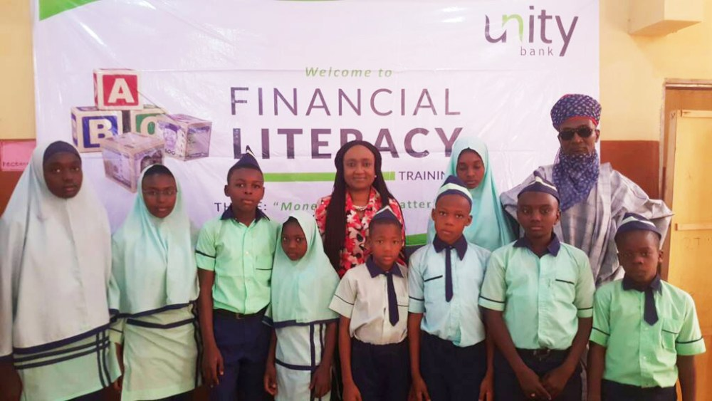 Unity Bank's Group Head, Corporate Planning & Strategy, Mrs. Titilayo Abraham and Proprietor and Board Chairman Royal Leads Academy, Alh Waziri Abdullahi Umar (Wazirin Gwandu) flanked by Students of Royal Leads Academy during the 2018 Financial Literacy Training facilitated in the school by Unity Bank Plc.