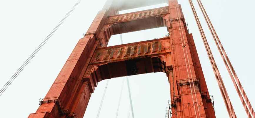 historic suspension bridge against cloudy sky