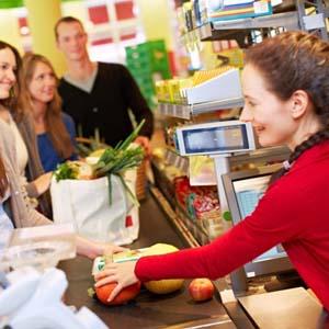 Junge Frau steht an Kasse bei Kassiererin im Supermarkt