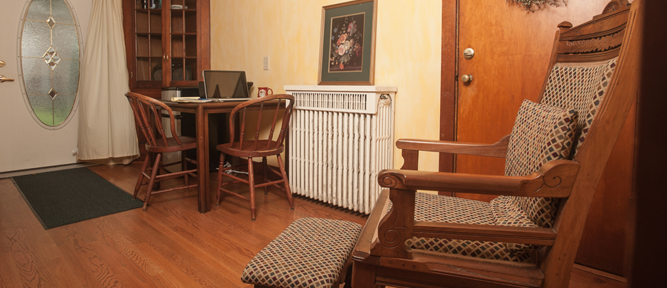 Sitting area with a wood table with two chairs and a laptop, old fashion tall wood chair with ottoman