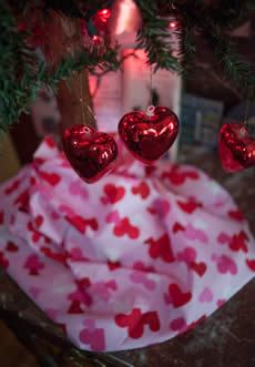 Tree with glass hearts ornaments with heart tissue paper under
