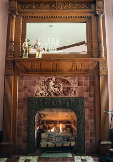Carved out wood and tile fireplace, very old gas run