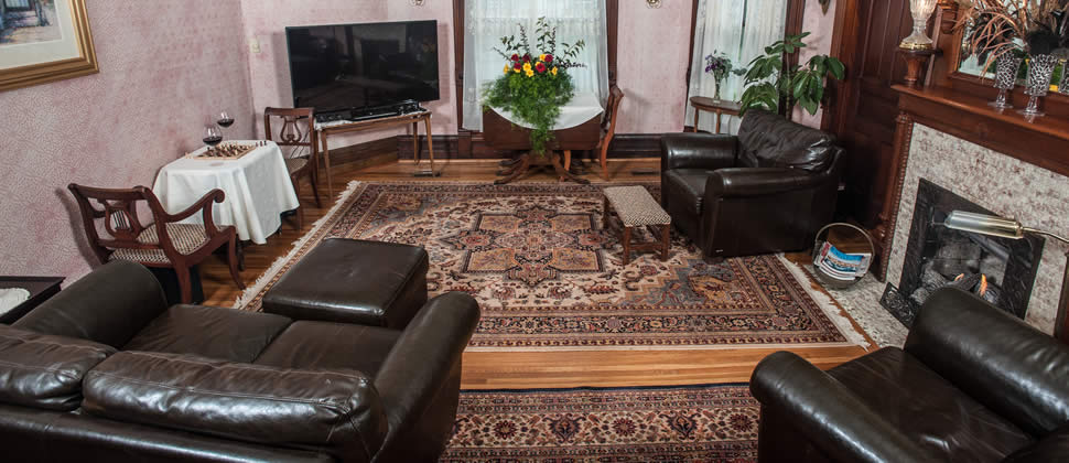 Loveseat and two chairs in leather in a sitting room with gas fireplace, paisley carpet in center with hardwood floors
