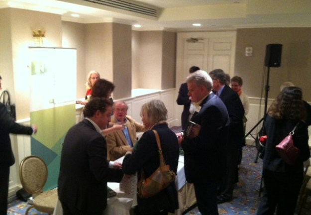 Simon Carswell, standing left talking with woman, and Donal Donovan, seated in tan jacket, sign copies of their books.