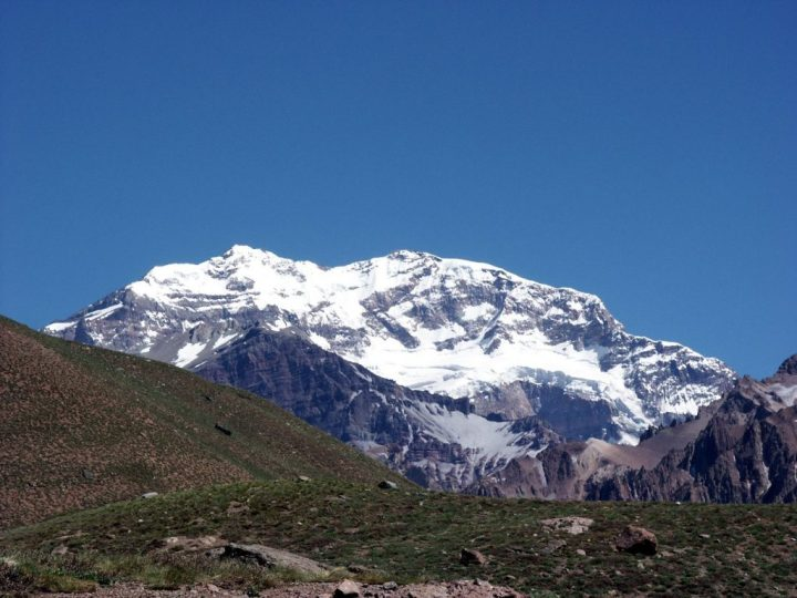 From the bottom end of the Horcones Valley Aconcagua is a mighty fortress of white rising up behind brown desert hills, smudged with green