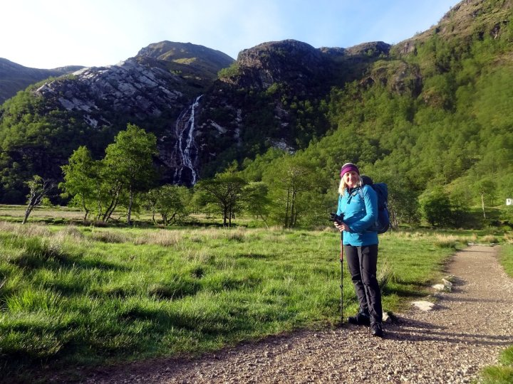 Edita in the wild camping meadow in Glen Nevis, with the waterfall of An Steall behind