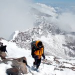 Me approaching Aconcagua's summit, with the South Face dropping away abruptly to the left behind me (Photo: Augusto Ortega)