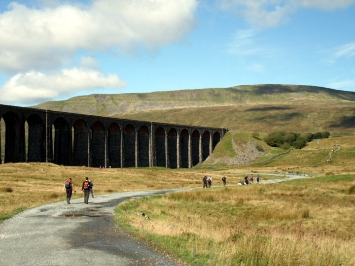 Walkers passing the Ribblehead Viaduct with Whernside behind