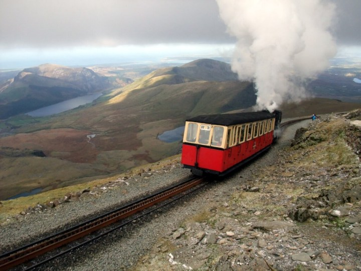 A Snowdon Mountain Railway train approaches Snowdon's summit. The Snowdon Ranger Path starts at the lake of Llyn Cwellyn in the top left corner of this photo.