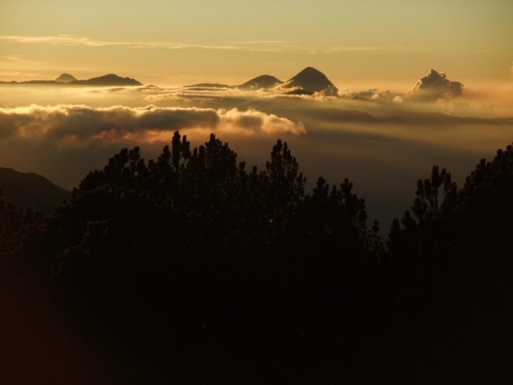 Dawn across eastern Guatemala, and a horizon which includes Volcan Santa Maria and erupting Santiaguito