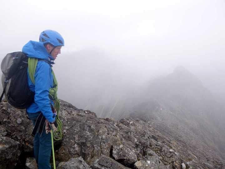 Dave on the summit of Sgurr Thearlaich, with the blurred outline of Sgurr Mhic Choinnich visible in mist behind