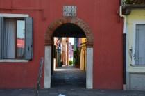 Torbogen und bunte Häuser in Burano, Venedig, Italien