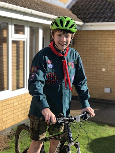 Matthew on his bike, in Scout uniform