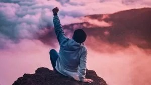 Man Raising Hand in Celebration on Mountain