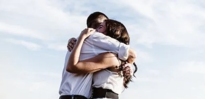 Husband and wife embracing in a hug with skyline