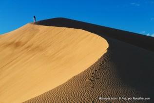 Um homem marroquino vestido com roupa tradicional em cima de uma duna de areia no deserto de Saara em Marrocos