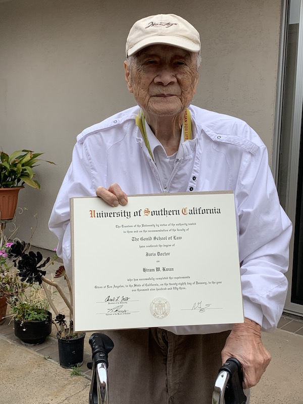Alumnus and Chinese American Hiram Kwan photographed holding his degree.