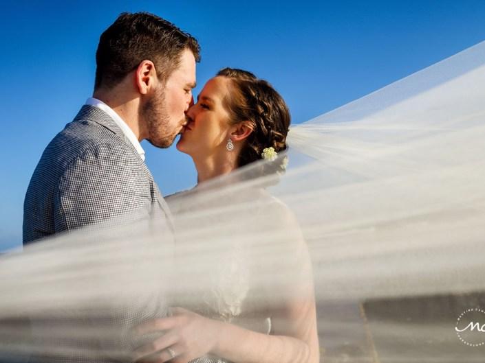 Veil shot. Bride and groom kiss. Hacienda del Mar wedding in Puerto Aventuras, Mexico. Martina Campolo Photography