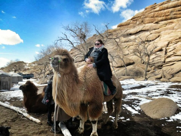 Anita looking just a little terrified, perched on a camel's back