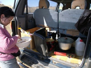 Oji cooking on a portable gas stove in the back of the van