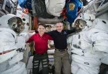 Los astronautas Anne McClain y David Saint Jacques fotografiados entre un par de trajes espaciales dentro de la esclusa de aire de Quest, donde se guardan los trajes espaciales. Image Credit: NASA