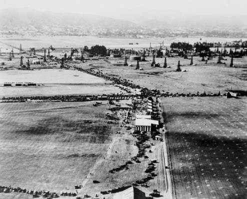 Aerial view looking north along Fairfax Ave at the intersection of Wilshire Blvd, showing Chaplin Airfield and DeMille Airfields, and oil wells, circa 1920