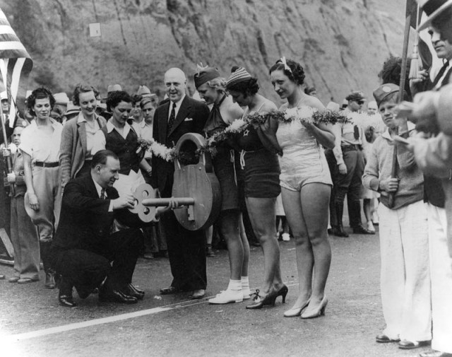 Three young women, holding a giant lock with key, pose on the California Incline during the opening of the Roosevelt Highway in Santa Monica