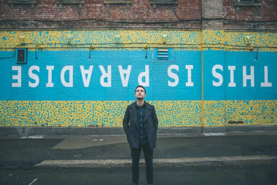 Joshua Hyslop stands in front of street art that says this is paradise. Hyslop released his latest folk album, Echoes.