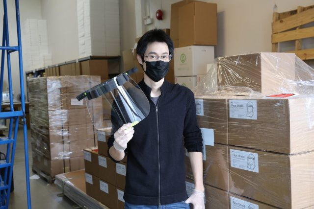 One of Tinkerine's employees shows a face shield for the deaf, in front of more boxes of face shields