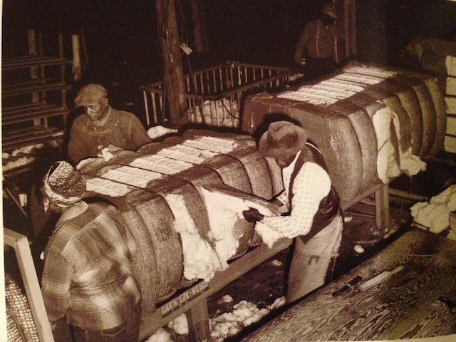 Workers handle cotton bales in a warehouse.