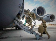 Aircrew assigned to Al Udeid Air Base, Qatar, carry their gear into a C-17 Globemaster III assigned to Joint Base Charleston, South Carolina, April 27, 2021, at Al Udeid AB. U.S. Air Force C-17s and other mobility aircraft around the U.S. Air Forces Central theater are assisting with the safe and orderly drawdown operations from Afghanistan. (U.S. Air Force photo by Staff Sgt. Kylee Gardner)