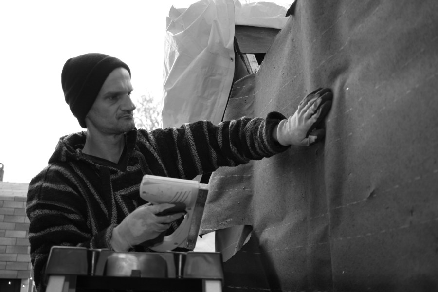 Joel adds tar paper to the outside of his shelter for weather proofing. Photo © 2016 Mary Anne Funk