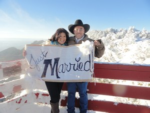 wedding couple at sandia crest holding just-married sign