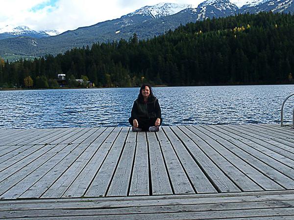 Reverend Marya OMalley meditating on mountain lakeside dock