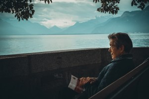 Old man with book gazes at mountain lake