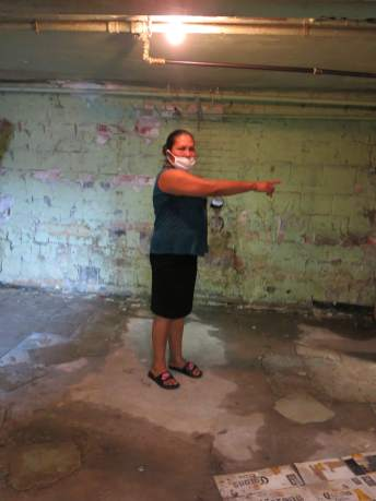 Norma Beltran steps over puddles of standing water in the basement of her apartment building at Bedford Station, which is also littered with trash and harbors mice and insects. Photo by Rosanne Skirble.