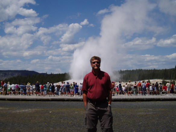 Old faithful with a geyser behind him