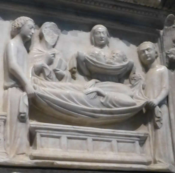 The bodies of Sts. Ermagora and Fortunatus without their heads. A man holds the two heads in a drape.