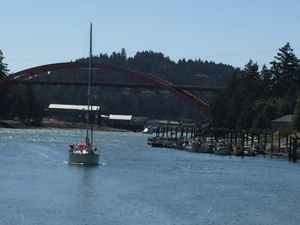 A sailboat that has passed under the bridge and continues down the channel