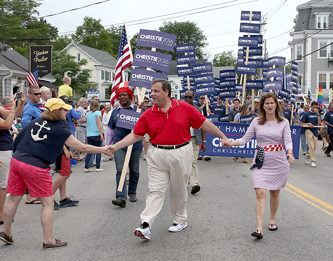 Republican presidential candidate New Jersey Gov. Chris Christie reaches out to shake hands as he and his wife wife Mary Pat walk through the downtown during the 4th of July parade, Saturday, July 4, 2015, in Wolfeboro, N.H. Associated Press/Mary Schwalm