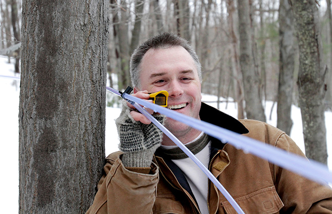 Paul Boulanger checks the downward pitch of a line while tapping trees on private land in North Andover.