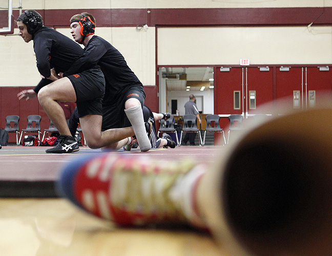 With his prosthesis resting at the edge of the mat, Greater Lawrence Tech wrestler Austin Poirier warms up with a teammate before their meet against Whittier Tech in Haverhill, Mass.