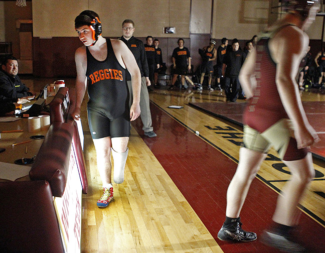 Wrestler Austin Poirier checks in at the scorers table before his match against Whittier Tech's John Michitson during their meet in Haverhill, Mass.