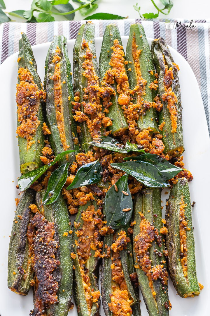 Stuffed Okra Recipe- bharwa bhindi served on a plate with loads of curry leaves.